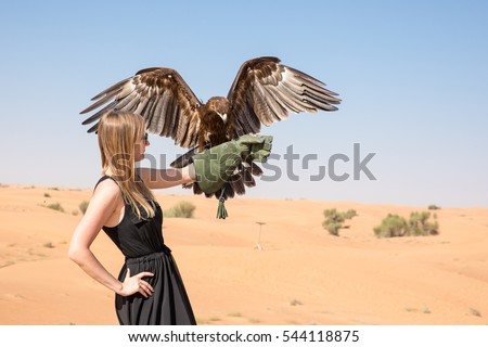 Shutterstock Greater spotted eagle (Clanga clanga) with a young female model during a desert falconry show in Dubai, UAE.