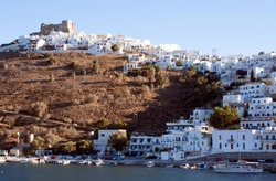 Greece, Astypalea island.  The harbour with the Querini Castle, atop the cliffs.  Below the castle are the whitewashed, cubist houses of the Hora.