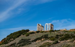 Greece Cape Sounio, Poseidon temple. Archaeological site of ancient greek temple ruins up on the hill, Athens Attica. Clear blue sky backgrpund, sunny day