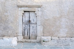 Greece, Cyclades. Folegandros island. Wooden shabby door with marble frame, old church at Chora town square. Traditional Cycladic chapel, whitewashed walls, space, template