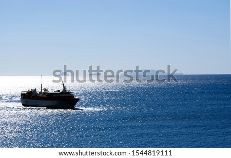 Greece, daybreak. The early morning ferry sails into harbor. A silver, peaceful sea as the ship navigates to the dock. Picture might illustrate travel or, specifically, Greek island hopping. #1544819111
