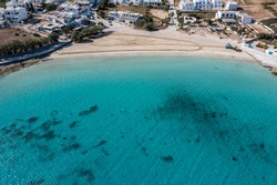 Greece, Koufonisi island, Pano Koufonisi Megali Ammos sandy beach aerial drone view. White traditional village buildings, calm turquise sea water background. Sand cleaning machine working.