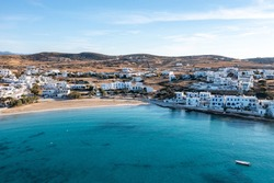 Greece, Koufonisi island, small Cyclades. Aerial drone view. Pano Koufonisi white traditional village buildings, Megali Ammos sandy beach. Calm turquise sea water, clear blue sky background.