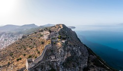 Greece, Nafplio city, Palamidi castle, Nauplion  landmark on a steep cliff, over old town, aerial drone view. Blue sky and calm sea background.
