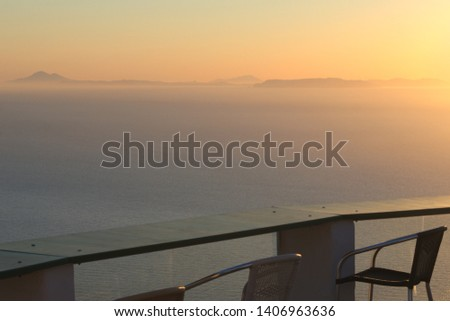Greece, the island of Sikinos in the Cyclades chain.  A view from a roof terrace with chairs and tables to the sunset over the sea an nearby islands. Pale pastel tones  with brown, crimson and orange