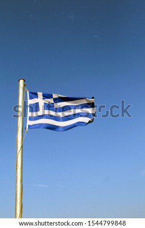 Greece, the national flag. Blue sky background. The colors of the sea and sky. Copy space. Picture may illustrate nationhood. Also a symbol of a destination to travel to. An emblem that says Greece. #1544799848