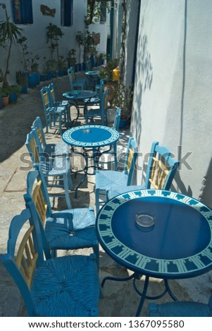 Greece the traditional and handsome island of Amorgos.  The old Chora with it's many pretty, winding alleys.  Tables and chairs by a cafe.