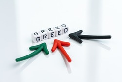 Greed and fear in stock market or money game and financial investment, multiple arrow pointing to cube block building the word GREED on clean white background.
