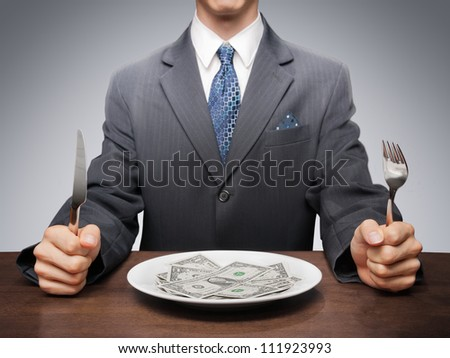 Greedy businessman eating banknotes symbolising consumerism.