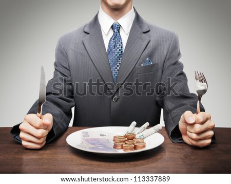 Greedy businessman eating money symbolising consumerism. - stock photo