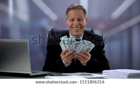Greedy businessman holding bunch of dollars, rejoicing easy income, high salary Photo stock ©