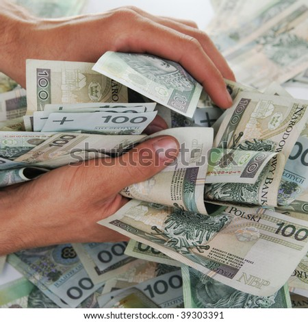 Greedy hand grabs money lot of polish banknotes
