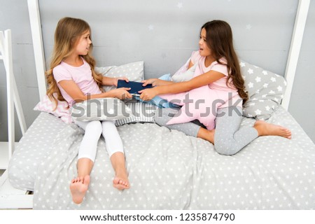 Greedy kids concept. Sisters relations issues. Share book with friend. Children in bedroom want read evening fairy tale. This is my book. She dont want to share her book. Sisters rivalry problem.