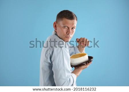 Greedy man hiding tasty cake on turquoise background Photo stock ©