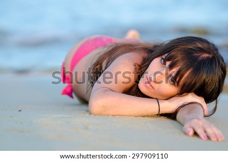 Greek amateur model late afternoon at the beach with bikini lying down with the stomach. Photo taken from top of her head