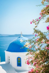Greek blue white church dome with colorful flowers at the island of Santorini Greece on an bright summer day