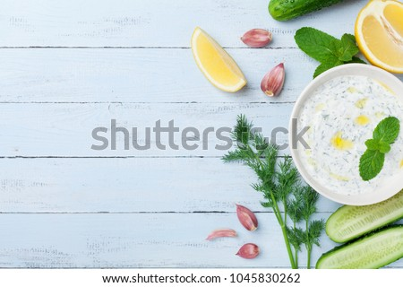 Greek dip sauce or dressing tzatziki from sour cream yogurt decorated with olive oil and mint on wooden table top view. #1045830262