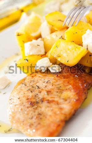 Greek dish with feta cheese, roasted potatoes, turkey steak and olive oil.