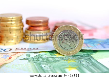 greek euro coin on bills