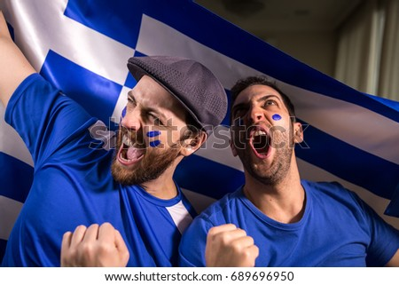 Greek fans holding the national flag - Shutterstock ID 689696950