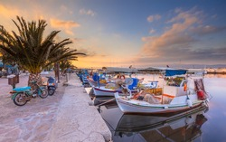 Greek fishing harbor scene with boats, palm trees and scooters at sunrise on a beautiful tranquil summer day in july