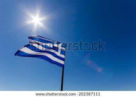 greek flag against the deep blue sky with sun and lens flair
