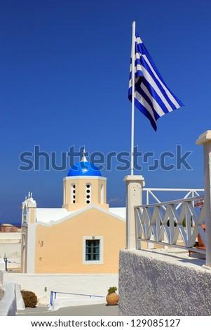Greek flag in front of traditional greek church in Oia village, Santorini Island, Greece