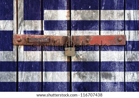 Greek flag on the background of old locked doors