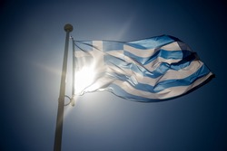 Greek flag waving before sun on blue sky, backlighting contre-jour
