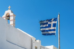 Greek flag waving on a must under strong wind against blue sky background, before a white Orthodox church, with belltower and Christian cross on top at Mykonos Island.