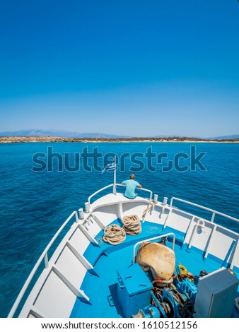 Greek flag waving on the bow of a boat sailing toward the island of Chrissi. The uninhabited island of Chrissi is available only by boat, an hour of cruise from Ierapetra, south of Crete.