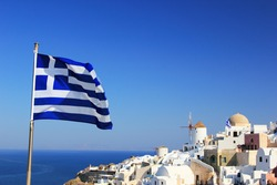Greek flag with overview on Oia on the island of Santorini in Greece