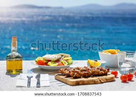 Greek food concept with farmers salad and souvlaki skewers in front of the sparkling, blue Aegean sea during summer time Foto d'archivio ©