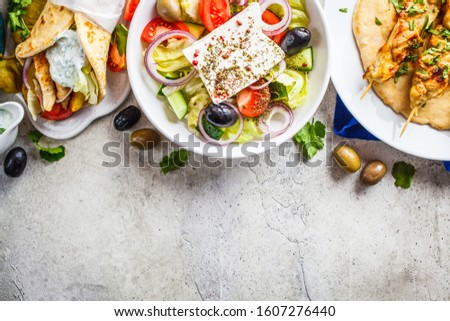 Greek food: greek salad, chicken souvlaki and gyro pita on gray background, top view. Traditional greek cuisine concept.