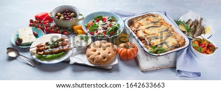 Greek food. Moussaka, meze, souvlaki, fish, pita, greek salad, tzatziki,  olives and vegetables. Traditional different types of greek dishes. Panorama, banner