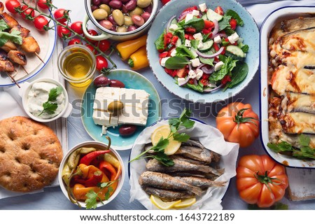 Greek food. Moussaka, meze, souvlaki, fish, pita, greek salad, tzatziki,  olives and vegetables. Traditional different types of greek dishes. Top view, flat lay