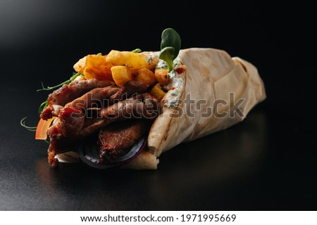 Greek gyros wrapped in pita breads on black background. Gyro pita, shawarma, take away, street food Stockfoto ©