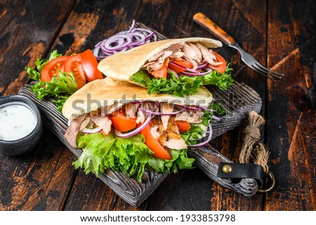 Greek gyros wrapped in pita breads with vegetables and sauce. Dark wooden background. Top view. Stockfoto ©