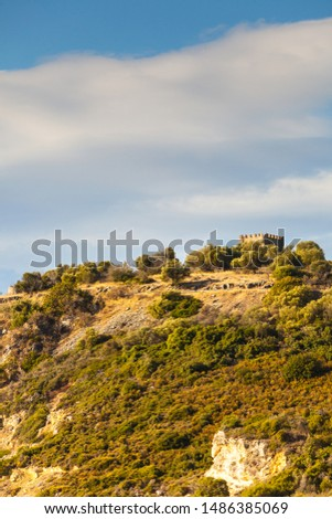 Greek idyllic hills with small shrubs of Mediterranean flora and little castle against cloudy sky. #1486385069