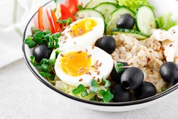 Greek inspired savory oatmeal with fresh cucumber, bell pepper, olives, lettuce, feta cheese, radish sprouts and soft-boiled egg for healthy breakfast
