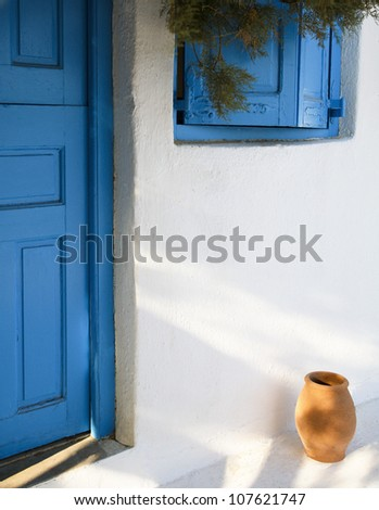 Greek island architecture typical cyclades architecture with small ceramic pot, blue door and shutters.
