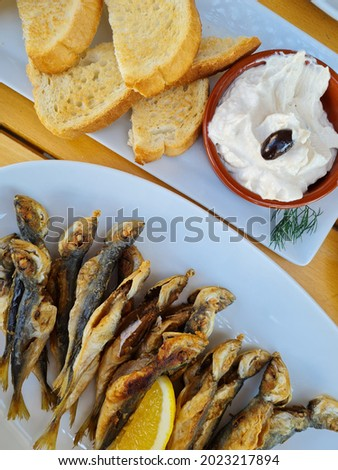 Greek meal, fried fresh small fish next to tarama caviar, baked bread and fresh friend potatoes, fries with cheese, bulgarian food, seaside meal, Mediterranean salad, tasty summer food, seafood Stok fotoğraf ©