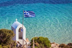 Greek National Flag over seascape, beautiful turquoise sea , summer travel vacation destination.