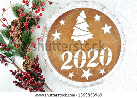Greek new year's cake for 2020 and artificial pine and red berries sticks