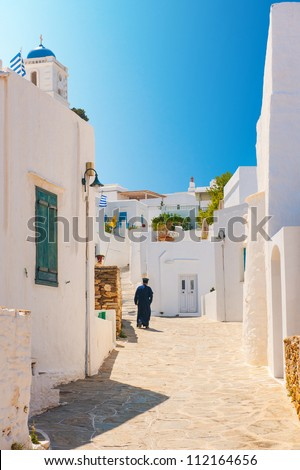 Greek Orthodox priest walking in an alleyway on the island of Sifnos