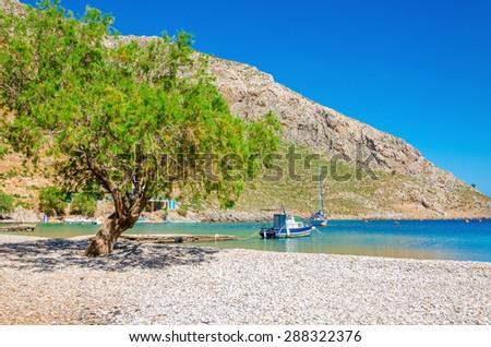 Greek pebble beach in a beautiful quiet bay, Greek Islands, Aegean Sea