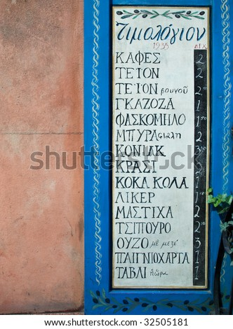 Greek restaurant menu written on the chalkboard - stucco wall in background