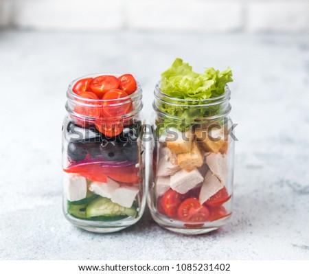 Greek Salad and Caesar salad in glass mason jar on gray background.Homemade healthy caesar salad and greek salad layered in jars.Healthy food, trendy modern food, diet concept, idea, recipe.Copy space
