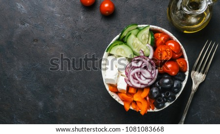 Greek Salad Bowl on dark black background, copy space. Above view of Bowl Greek Salad and ingredients. Trendy food. Idea, recept and concept of modern healthy food. Banner