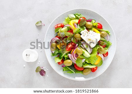 Greek salad. Fresh vegetable salad of cucumbers, tomatoes, olives, onion, bell pepper, feta cheese, lettuce and herbs and dressed with salt, pepper and olive oil. Horiatiki salad